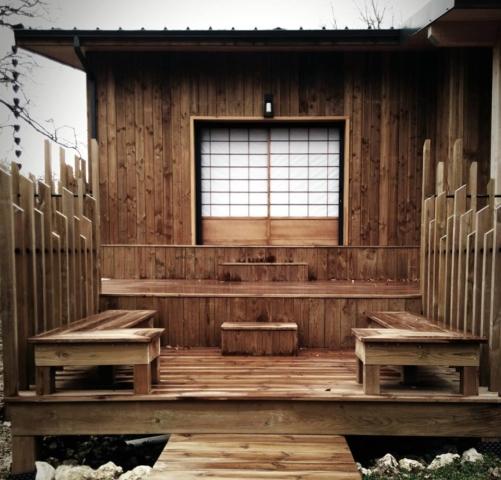 Vue extérieure du Ryokan en bois avec terrasses invitant à la méditation