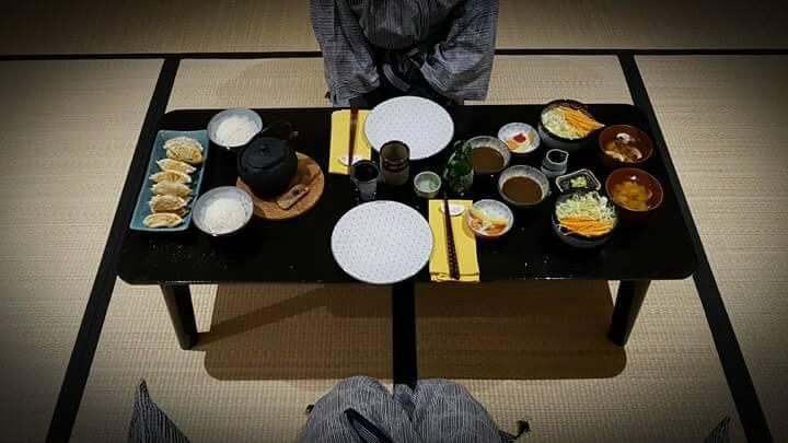 Repas dans le Ryokan sur table basse avec salade, soupe miso, gyosas, riz et thé